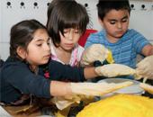 Gemeinsam basteln die Kinder eine Sonne aus Pappmaché.