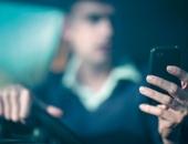 Ein Mann bedient während der Fahrt sein Handy.