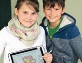 Zwei Kinder halten Tablets in der Hand.