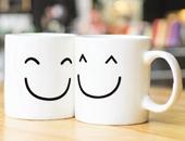 """Zwei Tassen mit lachenden Gesichtern stehen nebeneinander und """"lächeln sich an""""."""
