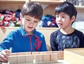 Zwei Jungen spielen gemeinsam mit einer Holzspielzeug.