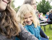 Ein Mädchen sitzt neben seiner Mutter auf einer Bank und lächelt in die Kamera.