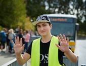 Ein Schüler, der als Buslotse arbeitet, trägt eine gelbe Warnweste.