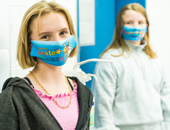 Zwei Schülerinnen tragen einen Mundschutz, den sie selbst für die Klasse entworfen haben.
